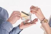 ritagliata colpo di coppia che tiene piccolo carrello e carta di credito in mani isolate su bianco