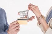 Fotografia ritagliata colpo di coppia che tiene piccolo carrello e carta di credito in mani isolate su bianco