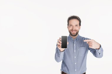 portrait of smiling bearded man pointing at smartphone with blank screen in hand isolated on white