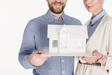 Partial view of smiling married couple with house model isolated on white stock vector