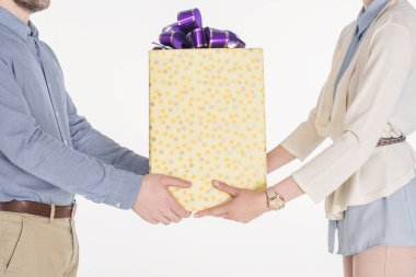 side view of couple holding wrapped gift in hands together isolated on white