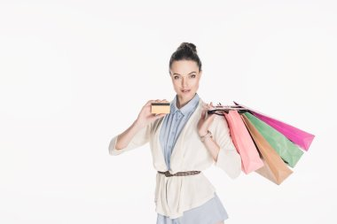 portrait of stylish woman with shopping bags showing credit card in hand isolated on white