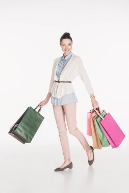 stylish cheerful woman with shopping bags in hands isolated on white