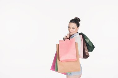 side view of stylish woman with shopping bags looking at camera isolated on white