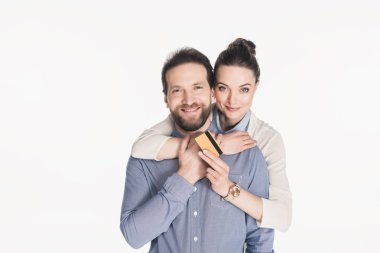 portrait of smiling woman with credit card hugging husband isolated on white
