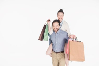 happy woman with shopping bags and husband piggybacking together isolated on white