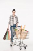 smiling woman with shopping bags and paper packages with grocery in shopping cart isolated on white