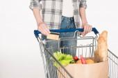 Fotografie částečný pohled ženy s kreditní kartou v ruce a do nákupního vozíku izolované na bílém papíru balíček s potravinami
