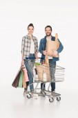Fotografie happy couple with shopping bags, paper packages with grocery and shopping cart isolated on white