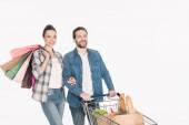 Fotografia Ritratto di sorridere coppia con borse della spesa e pacchetti di carta con la drogheria in carrello di acquisto isolato su bianco