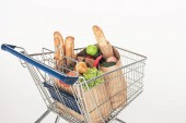 close up view of shopping cart with paper packages full of grocery isolated on white
