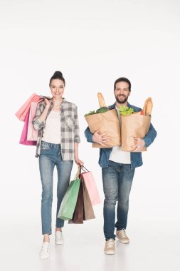 cheerful wife and husband carrying shopping bags and paper packages full of food isolated on white