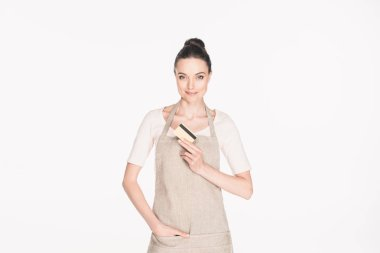 portrait of smiling woman in apron showing credit card in hand isolated on white