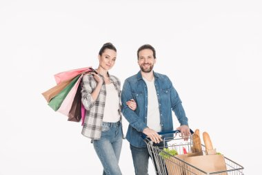 portrait of smiling couple with shopping bags and paper packages full of food in shopping cart isolated on white