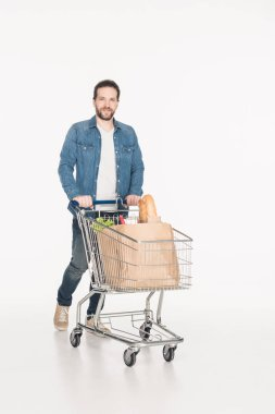 Smiling man with shopping cart full of paper packages with grocery isolated on white stock vector