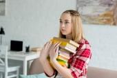 Fényképek tini diák lány a verem a könyvek otthon