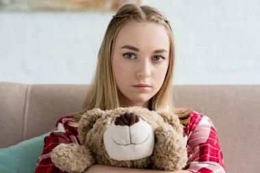 close-up portrait of beautiful teen girl embracing her teddy bear and looking at camera