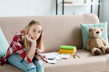 bored teen student girl with remote control watching tv while sitting on couch with book and notes