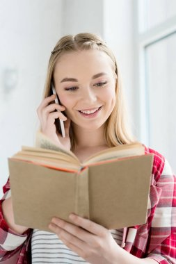 close-up portrait of happy teen student girl reading book and talking by phone