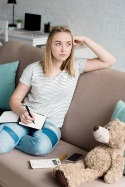 thoughtful teen student girl with notebook sitting on couch and looking away