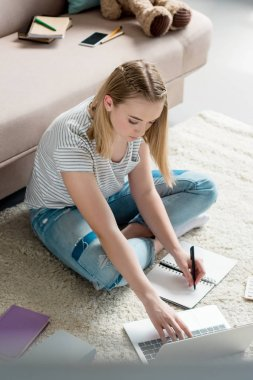 high angle view of teen student girl doing homework while sitting on floor