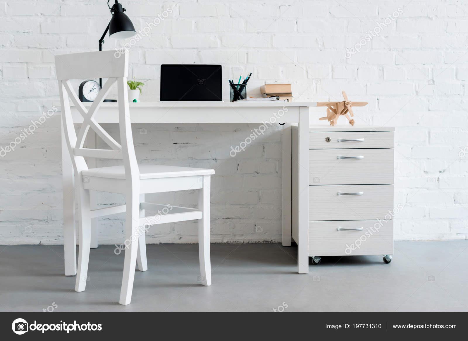 Bureau travail moderne avec ordinateur portable maison devant mur