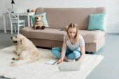 Photo teen student girl doing homework while sitting on floor with her dog