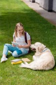 Photo happy teen student girl using tablet while sitting on grass with her dog