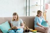 Fotografie matka a dcera sedí na gauči po hádce
