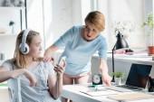 Fotografie matka nutí dceru udělat domácí úkoly, zatímco ona poslech hudby se sluchátky