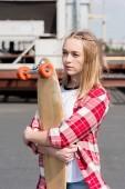 Krásné dospívající dívka v červené kostkované košili všeobjímající skateboard na střeše