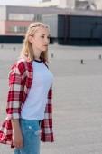 Stylový teen dívka v červené kostkované košili na střeše
