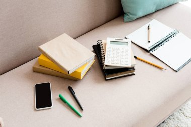 close-up shot of school supplies on couch at home