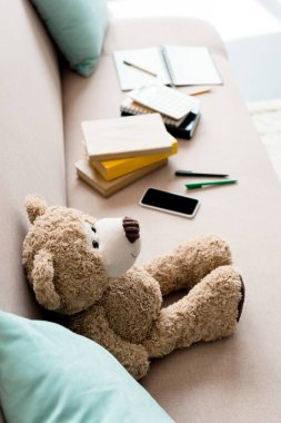 high angle view of teddy bear on couch with school supplies at home