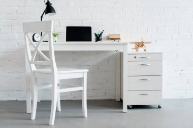 modern work desk with laptop at home in front of white brick wall