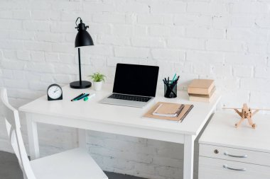 modern workplace with laptop at home in front of white brick wall