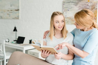 mother and teen daughter reading book together at home