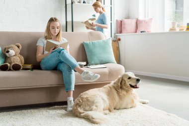 focused mother and teen daughter reading books together at home