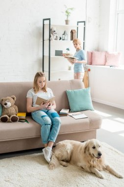 mother and teen daughter reading books together at home