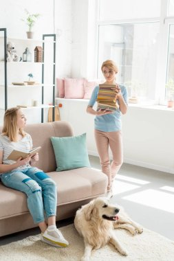 mother with stack of books helping her daughter with homework while their golden retriever lying on floor