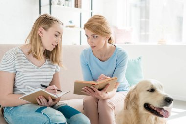 mother and teen daughter doing homework together while their golden retriever sitting on floor