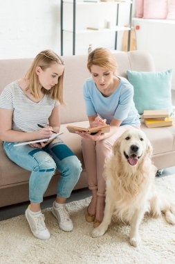mother and teen daughter doing homework together while their dog sitting on floor