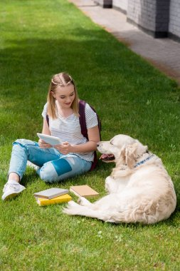 happy teen student girl using tablet while sitting on grass with her dog
