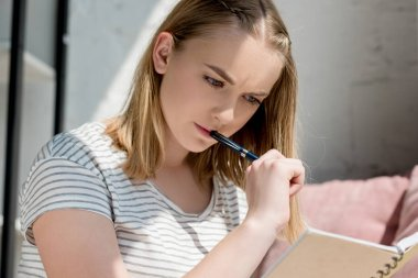 close-up portrait of concentrated teen student girl studying at home