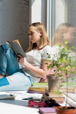 teen student girl reading book while sitting on windowsill