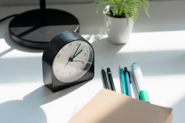 close-up shot of alarm clock with book and pens on workplace