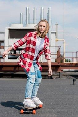 stylish teen girl riding skateboard on rooftop