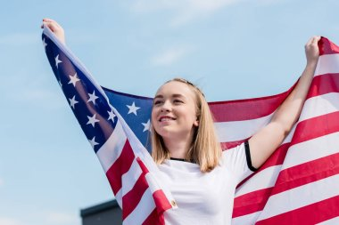 happy teen girl with usa flag in front of blue sky