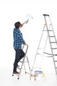 Fotografie zadní pohled člověka stojícího na žebříku barvou váleček izolovaných na bílém pozadí