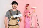 Fotografie usmívající se muž s válečkem a jeho přítelkyně, stojící za a malování zdi